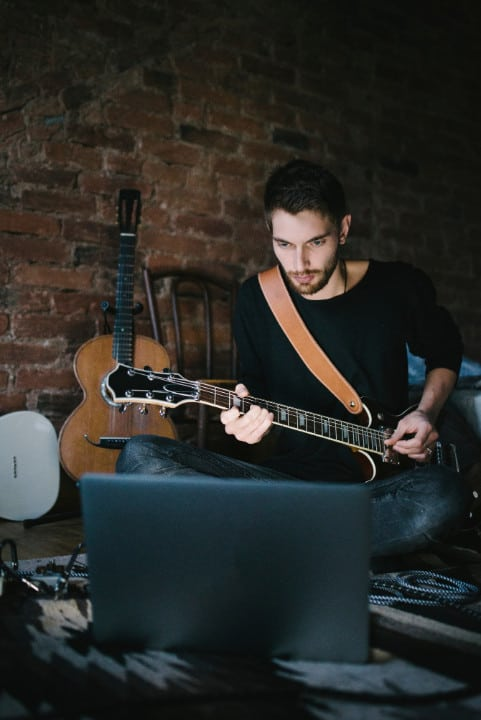 A guy reading a guitar tab from his computer.